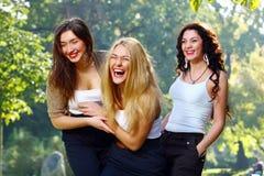 Les jeunes et belles amies ont l'amusement dans le stationnement Image libre de droits
