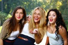 Les jeunes et belles amies ont l'amusement dans le stationnement Images libres de droits