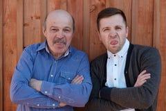 Les jeunes et vieux hommes montrent leur langue, dupant autour Images stock