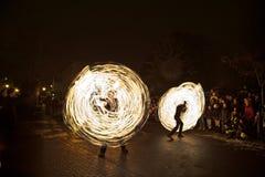 Les jeunes exécutent un spectacle du feu la nuit pour l'assistance Photographie stock libre de droits