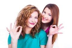Les jeunes expositions gaies de filles approuvent le geste Images stock