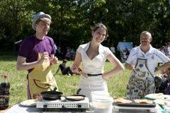 Les jeunes faisant cuire des crêpes Photos stock