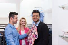 Les jeunes faisant des emplettes, clients de sourire heureux d'amis dans la chemise convenable de boutique de mode Photos stock