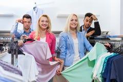 Les jeunes faisant des emplettes, femme de sourire heureuse de boutique de mode choisissant des vêtements, homme fatigué ennuyé Images libres de droits
