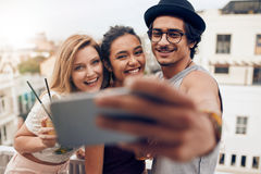 Les jeunes faisant la fête et prenant le selfie sur le dessus de toit Photographie stock libre de droits