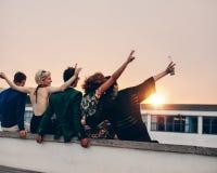 Les jeunes faisant la fête sur la terrasse avec des boissons Photo libre de droits