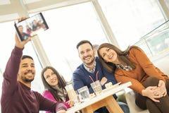 Les jeunes faisant le selfie en café Images stock