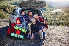 Les jeunes faisant le selfie sur le smartphone, penchement se reposant sur le tronc de la voiture de suv sur le fond de montagne  photo stock