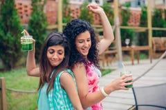 Les jeunes femmes ajoutent aux boissons saines dansant dehors Photos stock