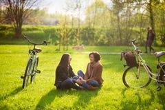 Les jeunes femmes avec du charme s'asseyent sur un parc vert de pelouse au printemps Images libres de droits