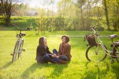 Les jeunes femmes avec du charme s'asseyent sur un parc vert de pelouse au printemps Photos stock