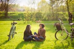 Les jeunes femmes avec du charme s'asseyent sur un parc vert de pelouse au printemps Photographie stock libre de droits