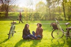 Les jeunes femmes avec du charme s'asseyent sur un parc vert de pelouse au printemps Images stock