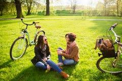 Les jeunes femmes avec du charme s'asseyent sur un parc vert de pelouse au printemps Image stock