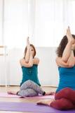 Les jeunes femmes avec les yeux fermés se reposant sur le tapis et méditent Image stock