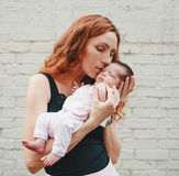 Les jeunes femmes belles embrasse le bébé nouveau-né Moment émouvant Photographie stock