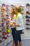 Jeunes femmes dans le département des chaussures de sports Photographie stock libre de droits