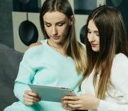 Les jeunes femmes détendant sur le salon parquettent regarder un ordinateur portable et rire de quelque chose sur l'écran Photos stock