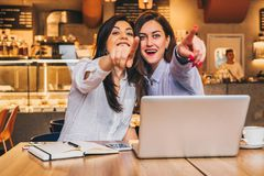 Les jeunes femmes d'affaires s'asseyent dans un café Les filles avec surprise joyeuse dirigent des doigts à ce qu'elles voient en Photo libre de droits