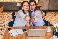 Les jeunes femmes d'affaires s'asseyent dans un café Les filles avec surprise joyeuse dirigent des doigts à ce qu'elles voient en Photo stock