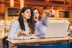 Les jeunes femmes d'affaires s'asseyent dans un café Les filles avec surprise joyeuse dirigent des doigts à ce qu'elles voient en Photographie stock libre de droits