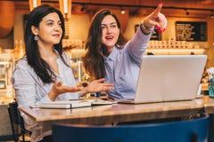 Les jeunes femmes d'affaires s'asseyent dans un café Les filles avec surprise joyeuse dirigent des doigts à ce qu'elles voient en Images libres de droits