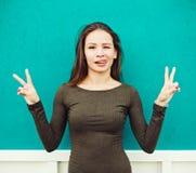 Les jeunes femmes d'une chevelure rouges collant sa langue et victoire d'exposition se connectent le fond vert de mur Image libre de droits