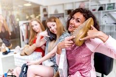 Les jeunes femmes de sourire s'asseyant dans un womenswear stockent jouer avec de nouvelles chaussures utilisant des chaussures c Images stock