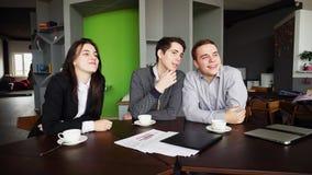 Les jeunes femmes et les camarades de classe d'hommes détendent du travail et de la causerie sur le résumé photographie stock