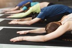 Les jeunes femmes et les hommes dans le yoga classent, détendent la pose de méditation photo libre de droits