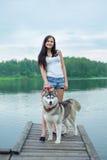 Les jeunes femmes et son costaud de chien s'assied en parc près du lac en été Photo stock