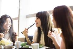 Les jeunes femmes groupent manger le pot chaud Image stock