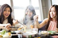 Les jeunes femmes groupent manger le pot chaud Images libres de droits