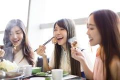 Les jeunes femmes groupent manger le pot chaud Photos libres de droits