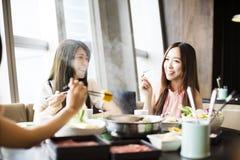 Les jeunes femmes groupent manger le pot chaud Photo stock