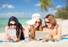 Les jeunes femmes heureuses avec le PC de comprimé l'été échouent Photos stock