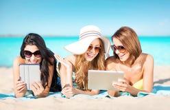 Les jeunes femmes heureuses avec le PC de comprimé l'été échouent Photographie stock