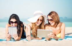 Les jeunes femmes heureuses avec le PC de comprimé l'été échouent Image stock