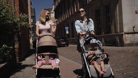 Les jeunes femmes heureuses de mères avec des poussettes de bébé descendent la promenade parlante de rue clips vidéos