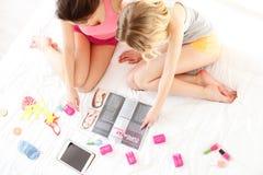Les jeunes femmes joyeuses sont intéressées par la mode Image stock