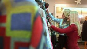 Les jeunes femmes minces achètent les vêtements à la mode à un centre commercial moderne banque de vidéos