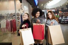 Les jeunes femmes multi-ethniques élégantes heureuses avec des paniers marchant dans le centre commercial avec l'eco de papier me Image libre de droits