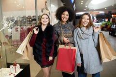 Les jeunes femmes multi-ethniques élégantes heureuses avec des paniers marchant dans le centre commercial avec l'eco de papier me Images libres de droits