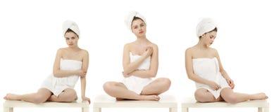 Les jeunes femmes ont enveloppé la serviette d'isolement sur le fond blanc Images libres de droits