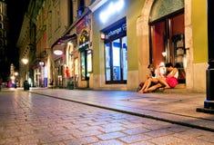 Les jeunes femmes s'asseyent sur le groung sur la rue de nuit Photos libres de droits
