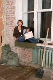 Les jeunes femmes s'assied à une fenêtre dans sale Photographie stock