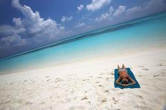 Les jeunes femmes se décolore au soleil sur la côte Image stock