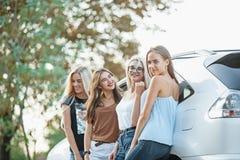 Les jeunes femmes se tenant près de la voiture Photographie stock libre de droits