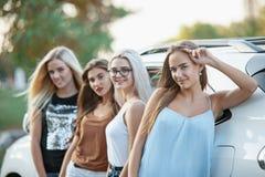 Les jeunes femmes se tenant près de la voiture Photos stock