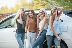 Les jeunes femmes se tenant près de la voiture Photo stock